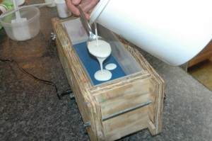 Pouring the white soap over the blue.