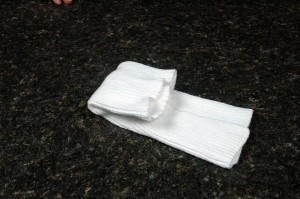 Folding the trifolded washcloth over one side of the soap.