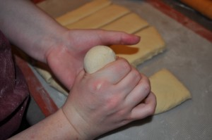 Pushing Dough through fingers to shape the roll