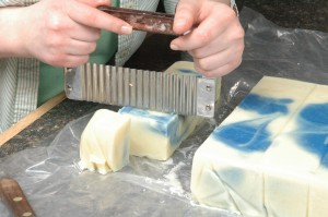 Cutting the manageable bars of swirled soap.